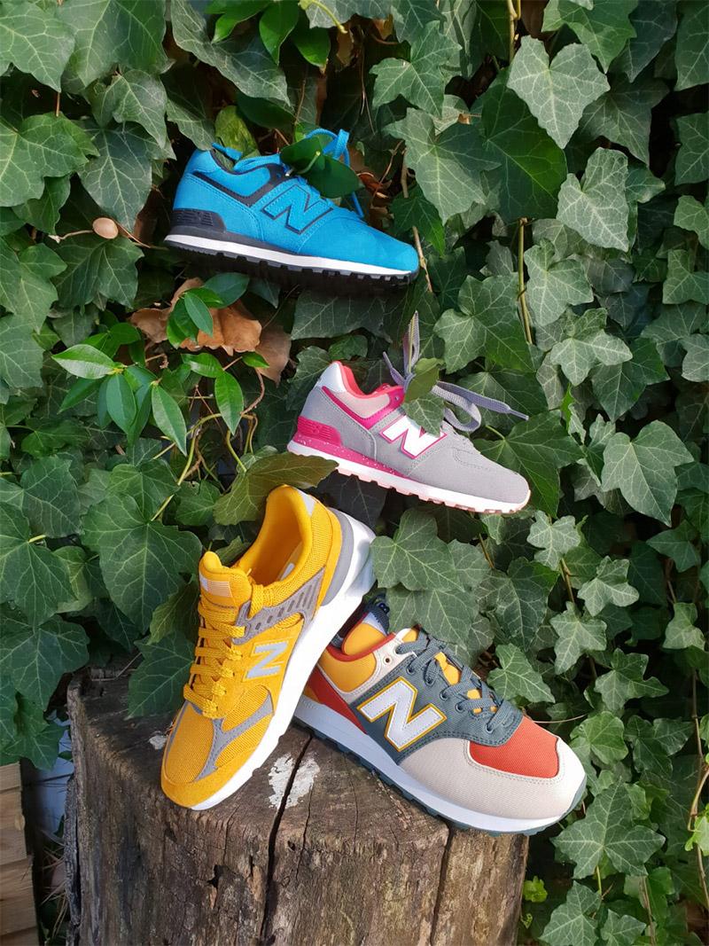 4 scarpe new balance appoggiate su un tronco con lo sfondo di edera