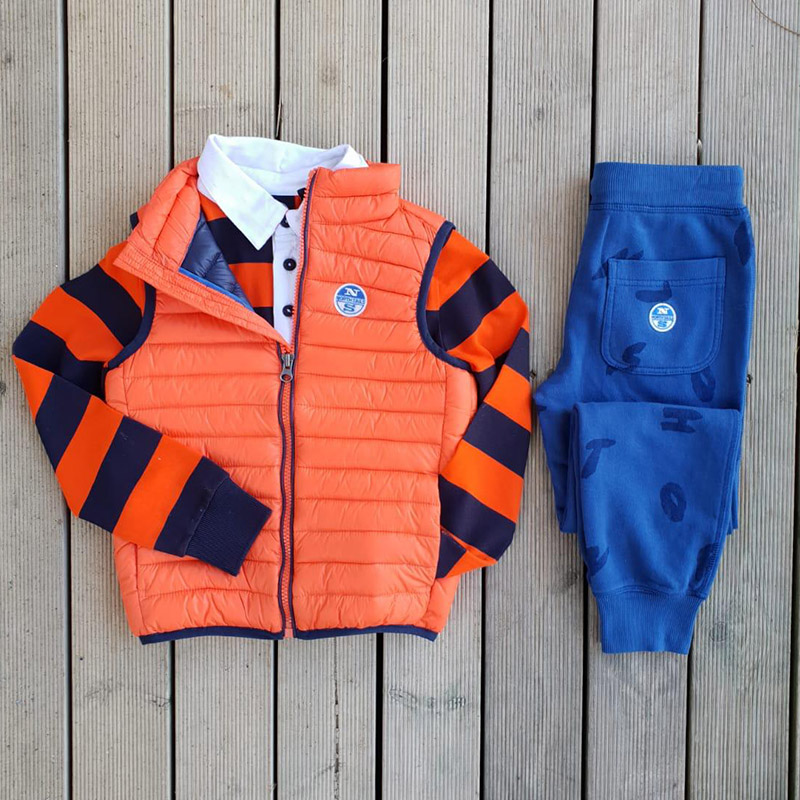 outfit per bambino del marchio north sails: pantalone felpa blu, gilet imbottito arancione, polo manica lunga rossa e blu