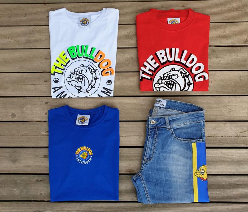 4 capi di abbigliamento del brand The Bulldog appoggiati a terra su pavimento di legno dell'Outlet Unionmoda